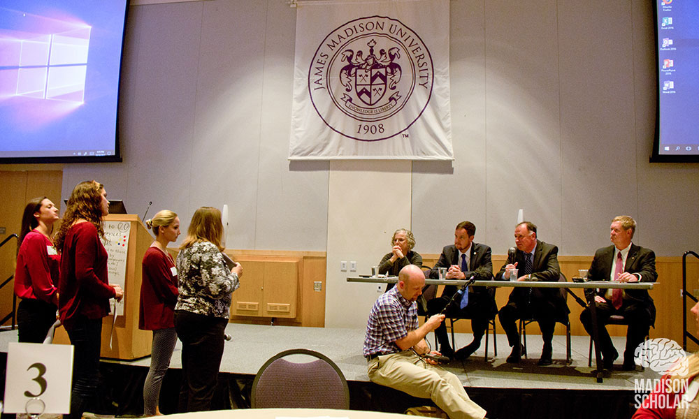 Panelists behind a table on a stage listen as students stand and discuss their proposal in front of the stage.