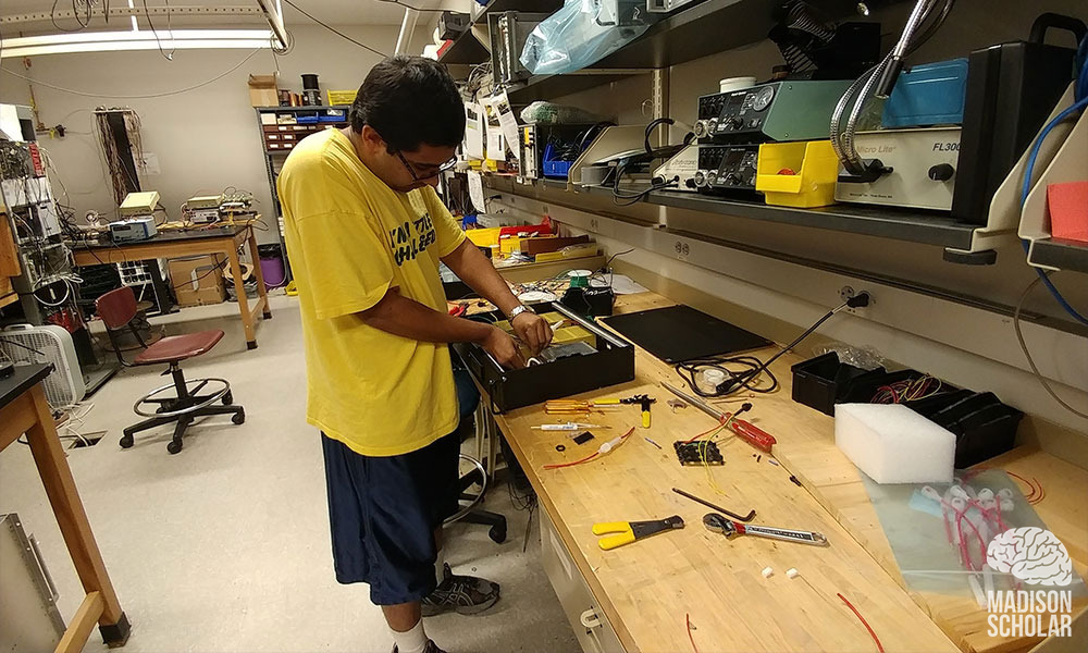 Premal Patel, dressed in yellow t-shirt and dark shorts, works on a power box at a work bench.