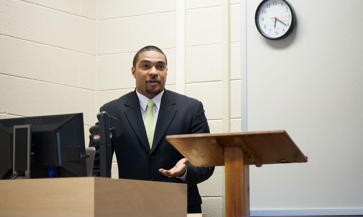 Former football player speaks from behind podium