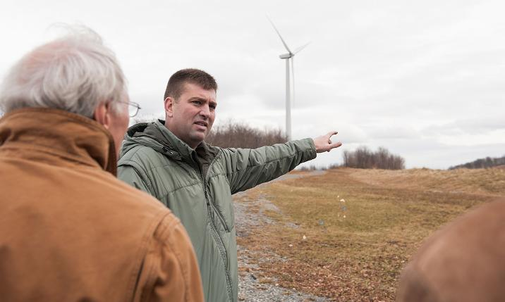 Wind farm manager points toward turbines as he discusses the operation.