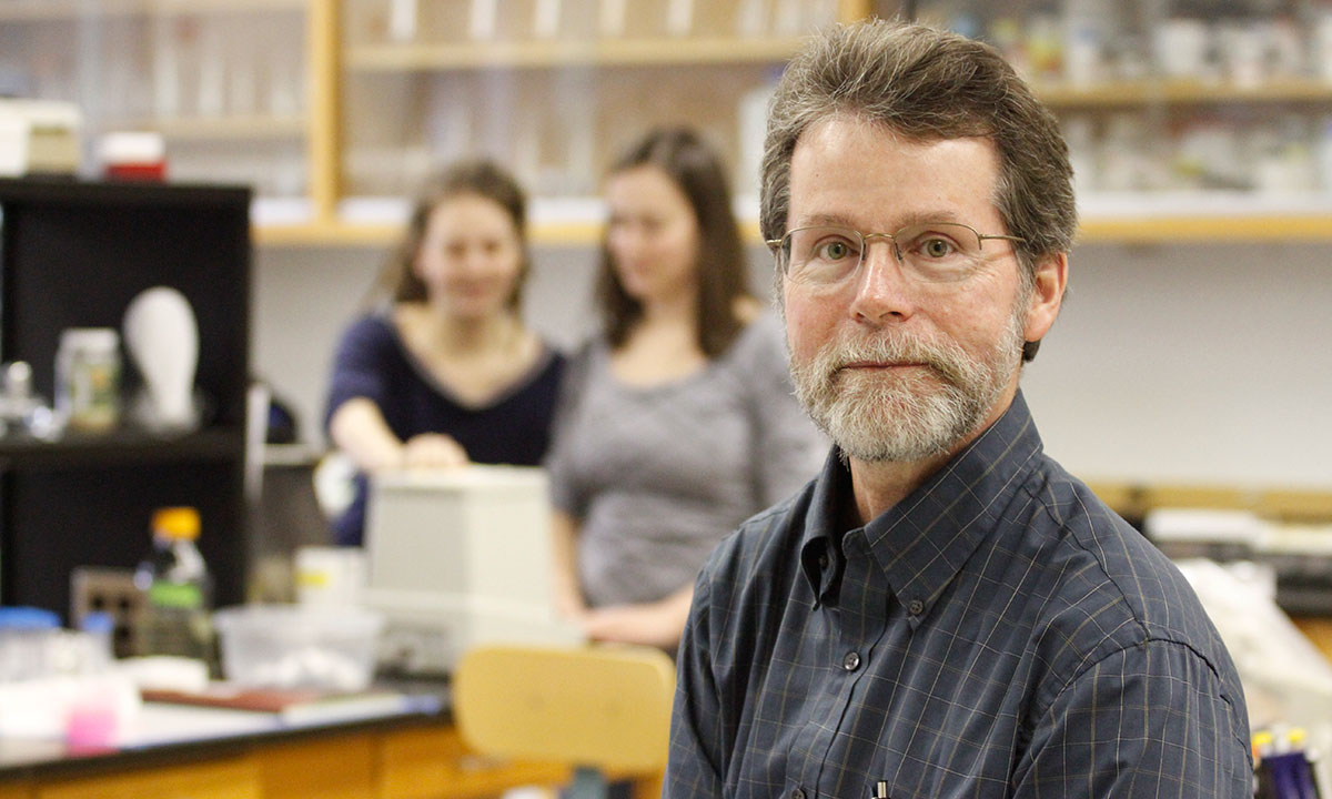 Dr. Reid Harris posing for the camera in his lab. Two students are in the background.