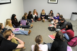 Photo of students sitting in a circle on the floor.
