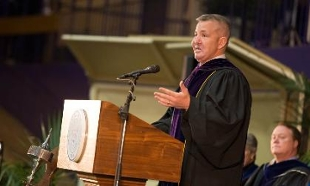Justin Constantine ('92) speaking on stage at JMU Dec commencement