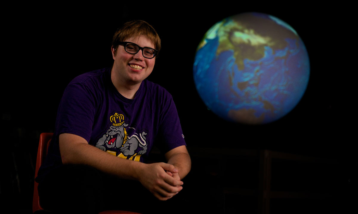 Adam White sits in a chair and looks at the camera while a lighted globe hangs behind and to his right in a darkened room.