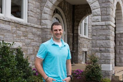 Andrew Marsh stands in front of JMU's Keezell Hall with its limestone exterior