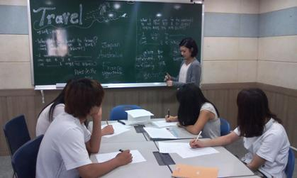 JMU student Sara Kim writes on a chalkboard as she conducts an English language class