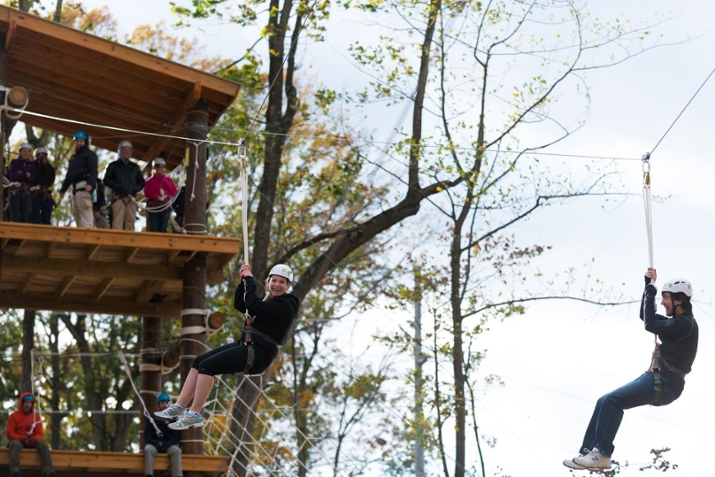 Students zip line from a high platform on the TEAM Challenge high-ropes course at University Park.