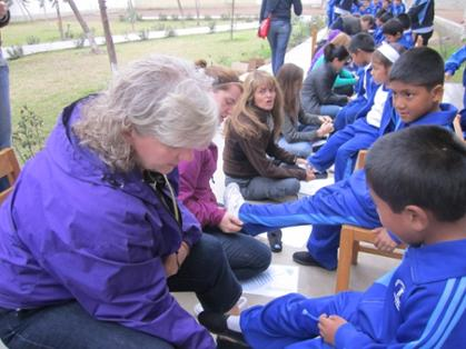 Maggie Evans fitting children with shoes in Peru on a TOMS Coprodeli Giving Trip.