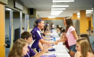 Male student shaking hands with female student over a table.
