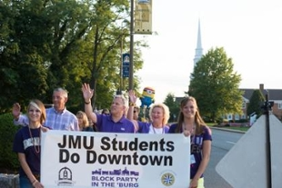 President Alger, his family and students carrying sign that reads JMU students do downtown; logo underneath says Block Party in the Burg