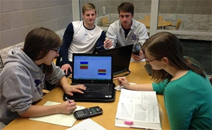 The four students in the capstone group sit around a table with a computer, a calculator and papers as they work on their project