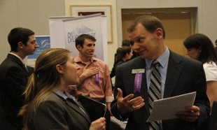 JMU's spring career fair, employer speaking to JMU student with other students and employers in background