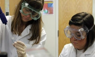 Students dressed in lab coats and goggles working with lab equipment.
