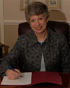 Formal portrait of Dr. Linda Cabe Halpern seated at desk