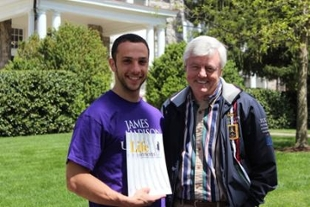 Andre Mortillo holding magazine Life lessons from JMU professors, standing with professor Bill Evans
