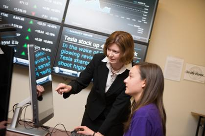Mary Gowan helps a female student navigate a Bloomberg business computer terminal at JMU's College of Business