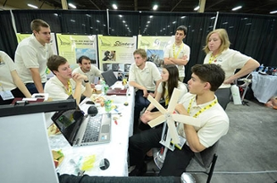 The JMU team, most seated around a table with a few others standing, discuss their project at the compeition.