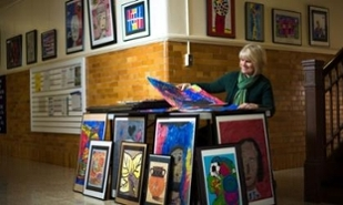 Dr. Deborah Carrington sorts artwork in preparation for display in JMU's Memorial Hall hallway