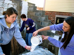 Two female students mixing paint in the foreground while a male student paints a cinderblock wall in the background.
