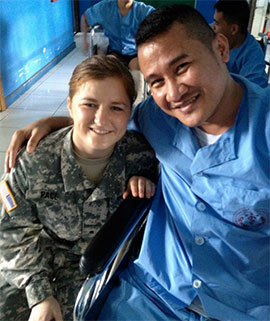 ROTC Cadet Erin Pace kneels beside a Philippines Military Medical Center patient
