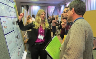 Kelly DuPont describes her research to a pair of judges in front of her poster.