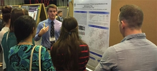 Student discusses his research while standing in front of his poster.