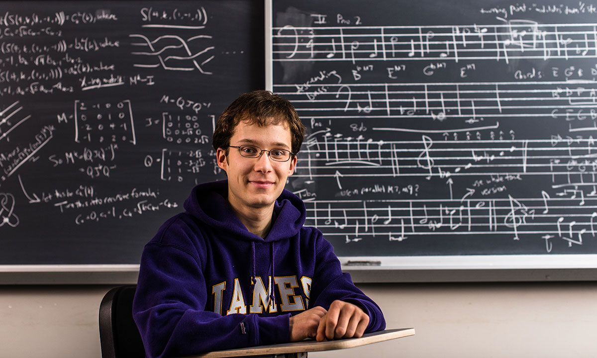 Ryan Stees sits at a student desk in a classroom looking at the camera, wearing a purple JMU sweatshirt. In the background is a blackboard with music written on one side and math formulas on the other.