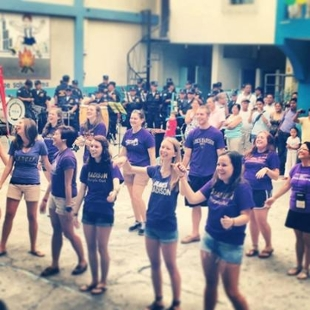 JMU students wearing JMU T-shirts dancing in Ecuador