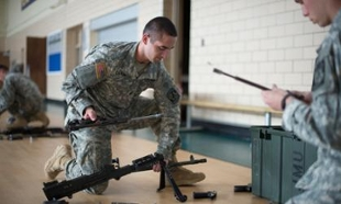 An ROTC cadet assembles a weapon with parts of other weapons laying around him on a gym floor