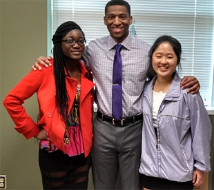 students stand together posing for the camera in an office, Owusu-Antwui on the left, Jones in the middle and Kim on the right as you look at the photo.
