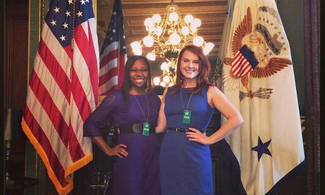 Raychel Whyte and Kim Johnson pose in front of two flags inside the White House.
