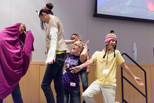 Several costumed students dance on stage during a team-building exercise.