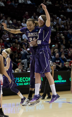JMU women's basketball players Jazmin Gwathmey (left) and Kirby Burkholder (right) celebrate their victory over Gonzaga University in the 2014 NCAA Women's Basketball Tournament.