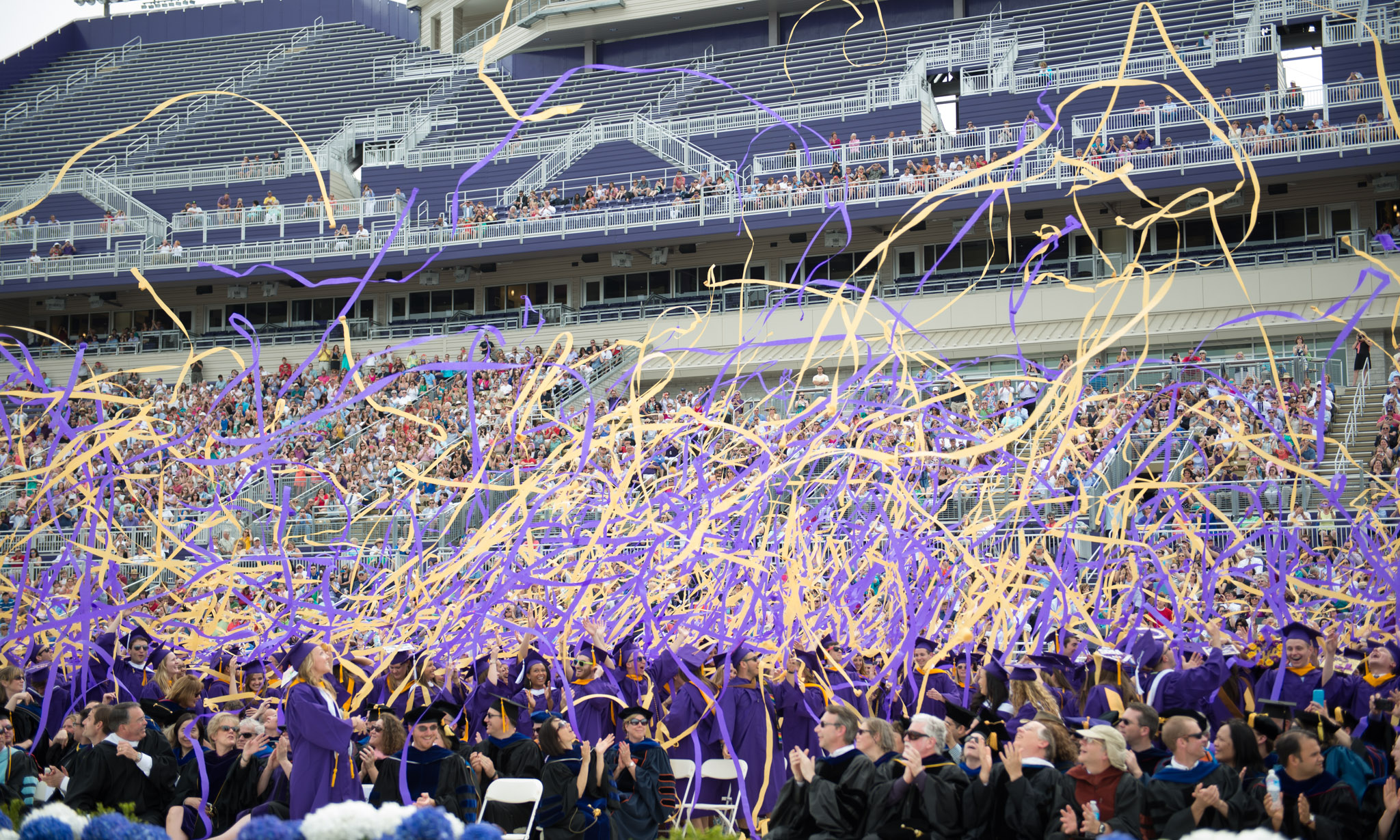 Class of 2014 graduates throw purple and gold streamers in celebration.