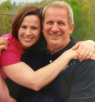 Informal portrait of Lisa Carnago and her father with her arms encircling him