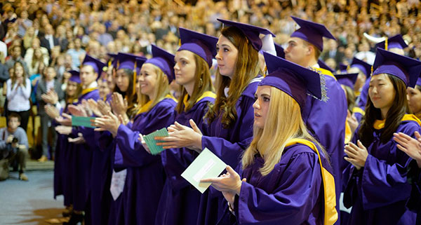 A small group of JMU graduates in purple academic gowns listen to commencement speech