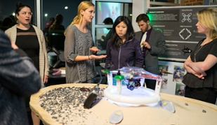 Students in background discussing drone in the foreground on a display that looks like a riverbed.