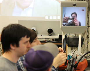 Fred Briggs holding a curved piece of a drone near his face appears on a monitor in front of a physics lab while students work on their projects.