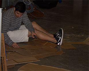student sitting on the floor, looking down at project, surrounded by pieces of cardboard.