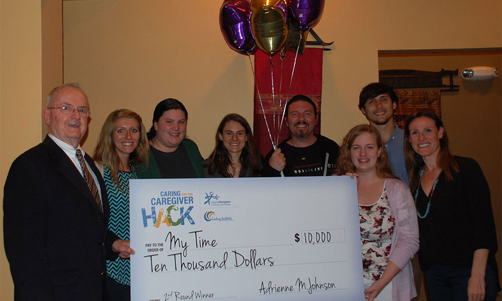 Winning team poses for the camera with several members holding a large check for $10,000.