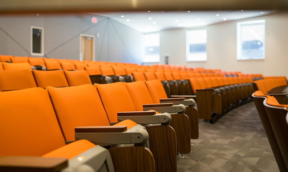 Rows of empty orange seats in one of the large lecture halls