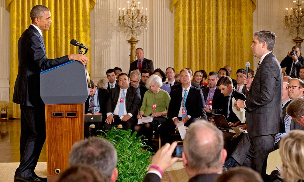 Jim Acosta facing President Obama from the audience. Obama who is standing behind a podium.