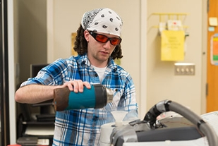 Male student wearing goggles in science lab