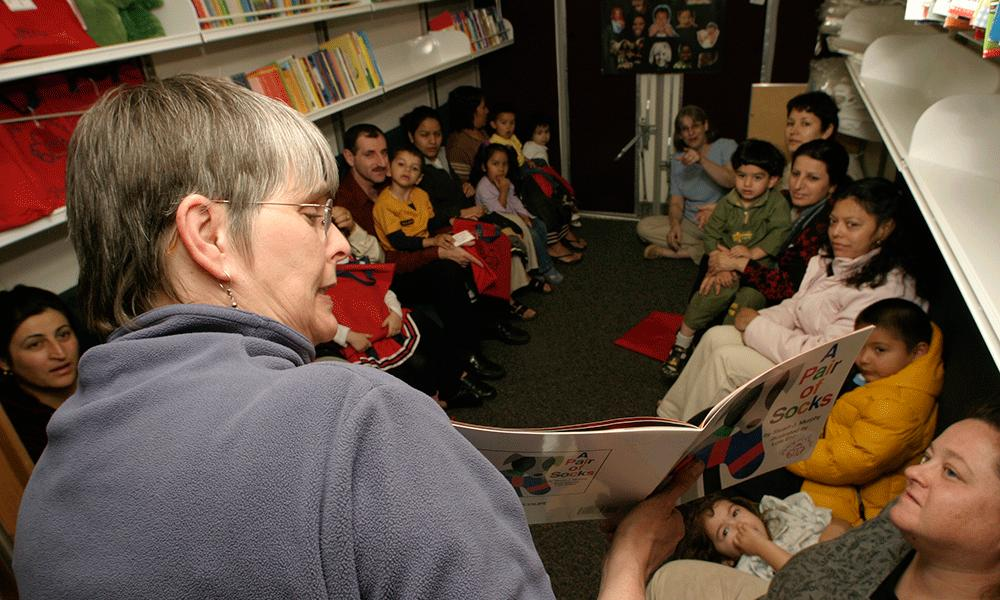 Photo of Pat Kennedy reads a story at a neighborhood bus stop.