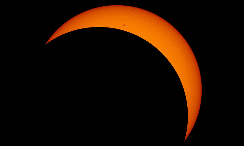 photo of an eclipse showing an orange sun mostly covered by the dark disc of the moon.