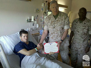 chapman in hospital bed receiving award from officers