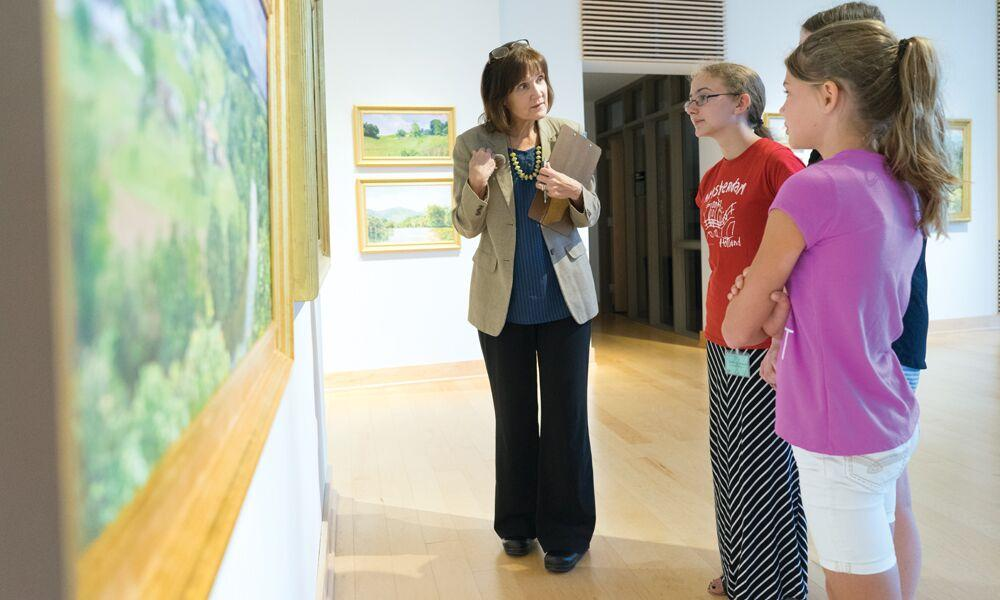 Professor Schwartz talks to girls viewing a painting in a gallery
