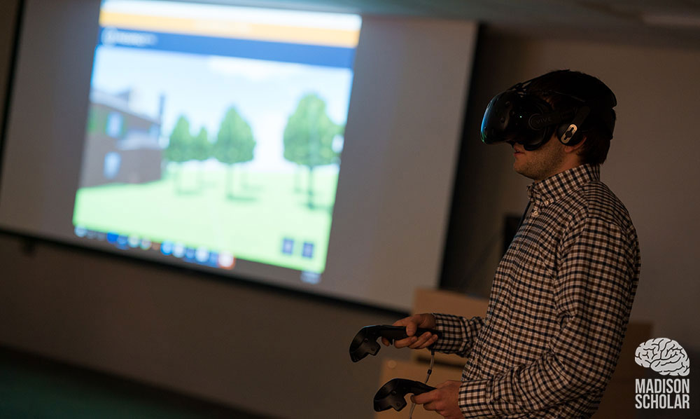 Student wearing VR goggles while giving presentation