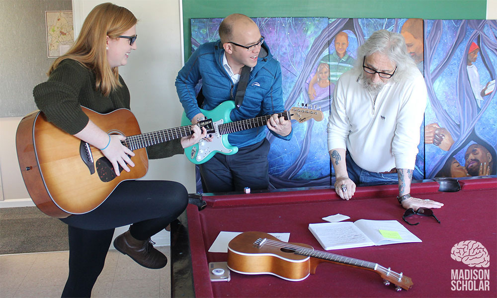David Stringham and student with guitars while Gemeinschaft resident looks at paper on pool table