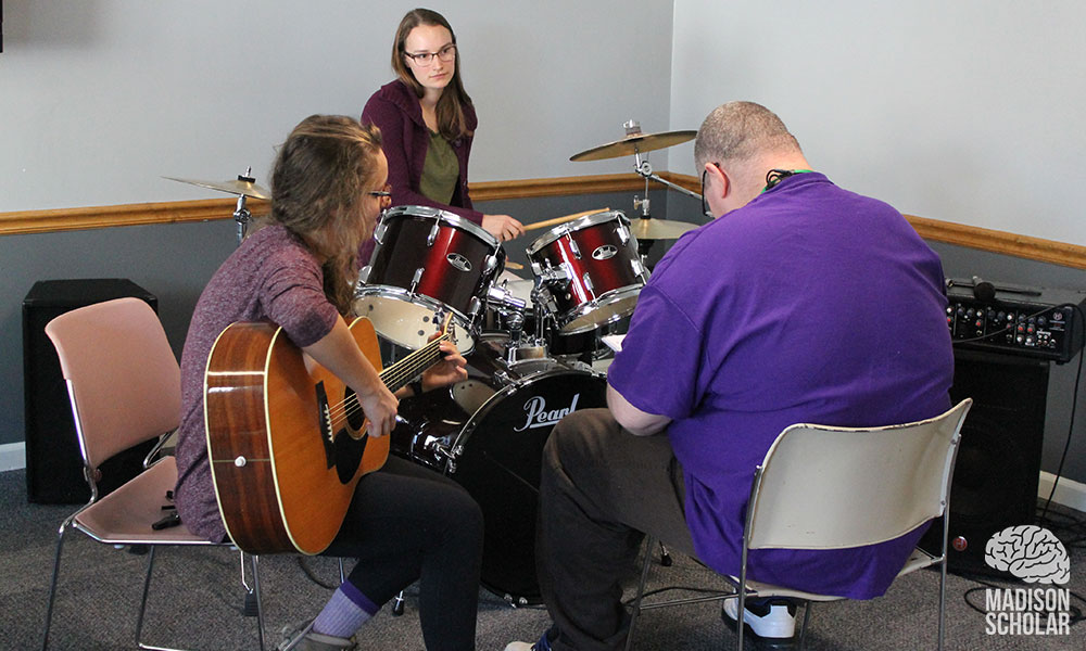 a student on drums and another with a guitar work with a Gemeinschaft resident who is also seated with his back to the camera.